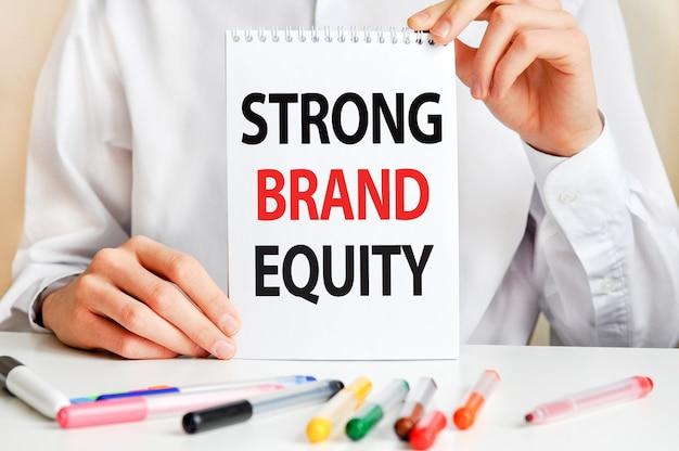 Ein mann in einem weißen hemd hält ein stück papier mit dem text: strong brand equity.