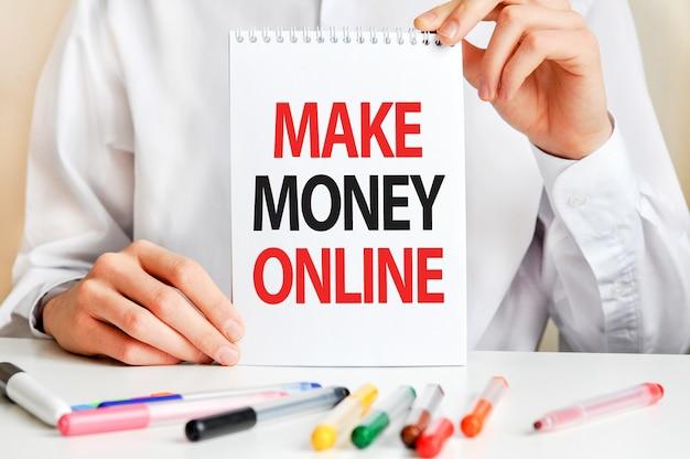 Ein mann in einem weißen hemd hält ein stück papier mit dem text: verdienen sie geld online
