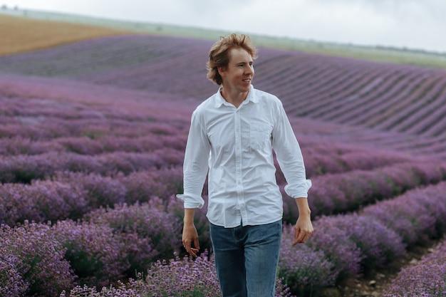 Ein mann in einem weißen hemd in einem lavendelfeld