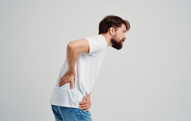 Ein mann in einem weißen t-shirt berührt seinen rücken mit schmerzen in der handwirbelsäule