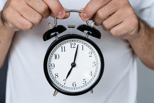 Ein mann in einem weißen t-shirt hält einen stilvollen schwarzen wecker mit einer glocke. auf dem wecker der anfang des achten. zeit aufzustehen.