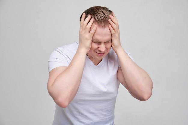 Ein mann in einem weißen t-shirt massiert sich mit den händen den kopf. das konzept des tiefen stresses aus lebensproblemen.