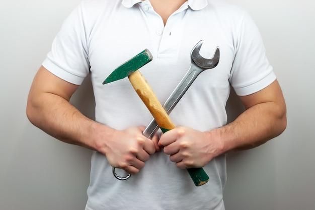 Ein mann in einem weißen t-shirt mit hammer und schraubenschlüssel