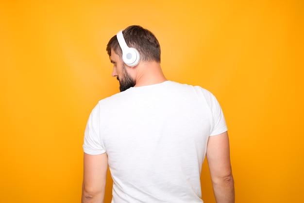 Ein mann in einem weißen t-shirt mit weißen kopfhörern auf dem kopf steht mit dem rücken.
