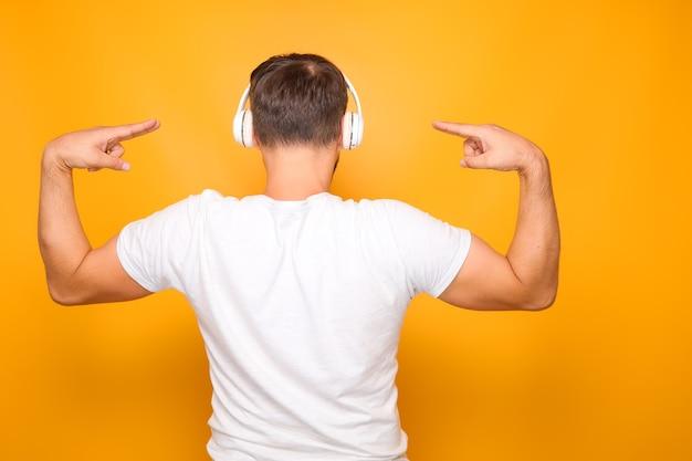 Ein mann in einem weißen t-shirt steht mit dem rücken und hört musik, während er gut tanzt.