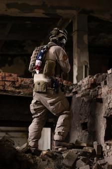 Ein mann in einer amerikanischen militäruniform steht in einem baufälligen gebäude auf einem stapel von zimmern airsoft