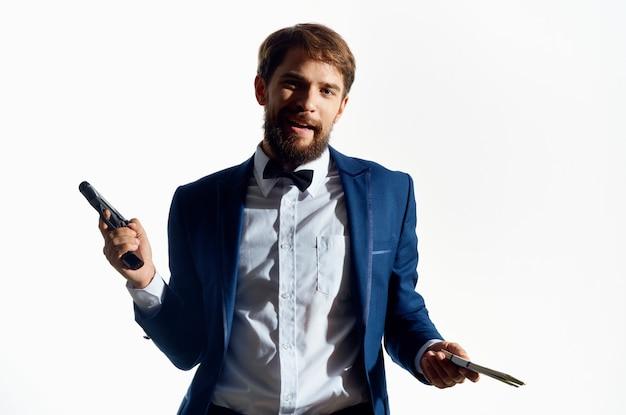 Ein mann in einer anzugmeisterwaffe, die geldmafia hält. hochwertiges foto