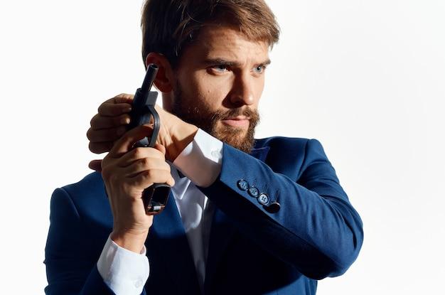 Ein mann in einer anzugmeisterwaffe, die geldmafia hält.