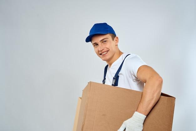 Ein mann in einer arbeitskleidung, der pappkartons lädt und dienstleistungen erbringt. hochwertiges foto