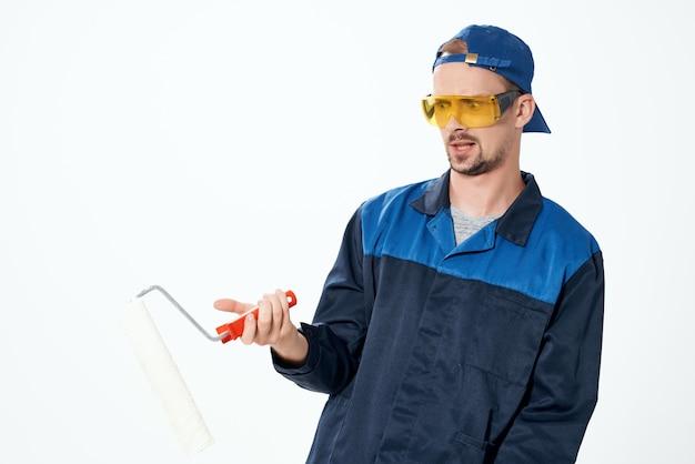 Ein mann in einer arbeitsuniform, der die wände streicht und das haus repariert