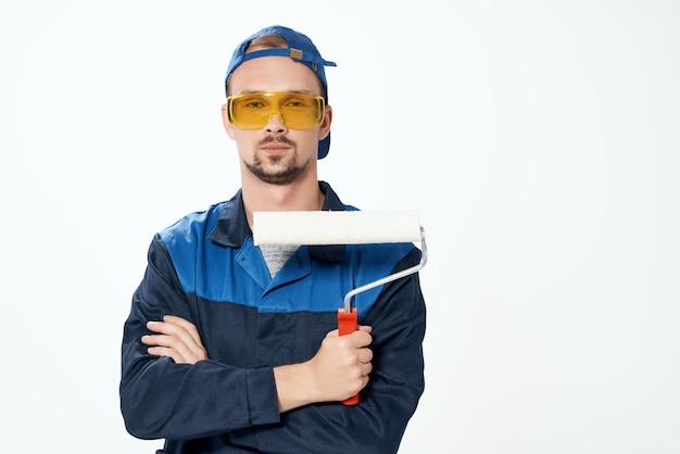 Ein mann in einer arbeitsuniform eine walze zum streichen von wänden in seinen händen dekorationsreparatur. foto in hoher qualität