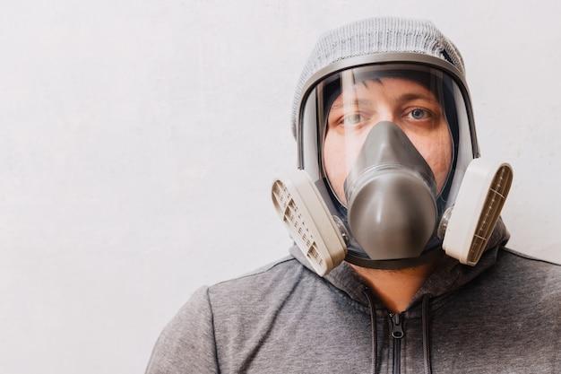 Ein mann in einer atemschutzmaske mit einem erhöhten schutz vor schädlichen umweltfaktoren. vollmaske.