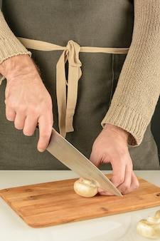 Ein mann in einer dunklen schürze schneidet einen champignon auf einem holzbrett.