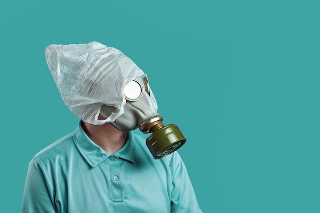 Ein mann in einer gasmaske und in einer plastiktüte auf seinem kopf, konzept des umweltschutzes vor verschmutzung