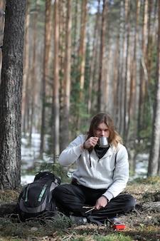 Ein mann in einer kampagne trinkt tee. ein junger reisender im wald kampierte und warmes frühstück in der natur. der naturforscher trinkt heißen frischen tee, der auf offenem feuer gekocht wird.