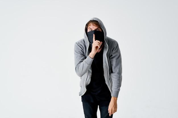 Ein mann in einer kapuze in einer maske einbruchdiebstahl anonymitätskriminalität