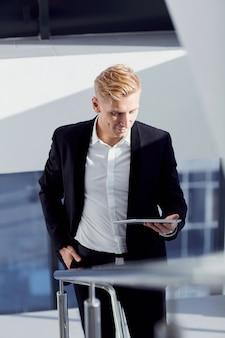Ein mann in einer klage mit tablette in seiner hand das büro