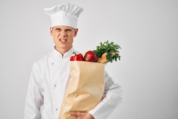 Ein mann in einer kochuniform mit einem paket lebensmittellieferung eines restaurantdienstes