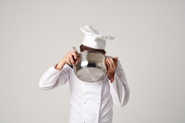 Ein mann in einer kochuniform mit einer pfanne in der hand kocht servicearbeit