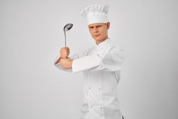 Ein mann in einer kochuniform mit einer schöpfkelle in den händen, die essen auf hellem hintergrund zubereitet