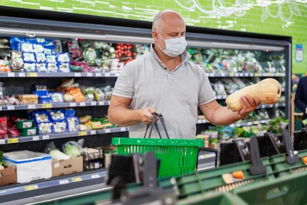 Ein mann in einer medizinischen maske pflückt gemüse in einem supermarkt. große auswahl. gesunde ernährung und vegetarismus. coronavirus pandemie.