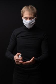 Ein mann in einer medizinischen maske zeigt, wie man seine hände mit einem antiseptikum behandelt. coronavirus schutz.