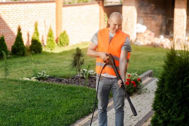 Ein mann in einer orangefarbenen weste putzt eine grasfliese in seinem garten in der nähe des hauses.