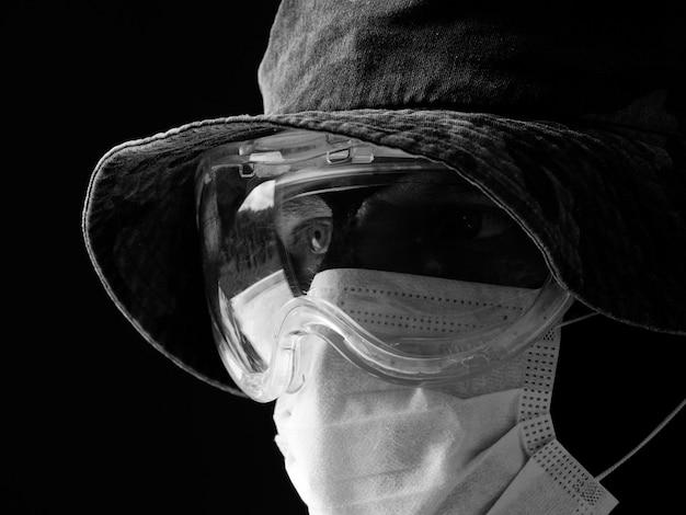 Ein mann in einer schützenden und medizinischen maske, einem tarnhut aus panama und einer schwarzen sturmhaube.
