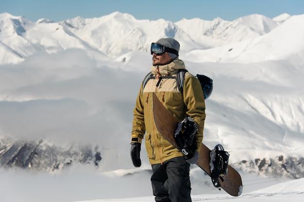 Ein mann in einer schutzbrille und einem warmen anzug mit einem snowboard in den händen steigt auf die strecke gegen die schneebedeckten berge