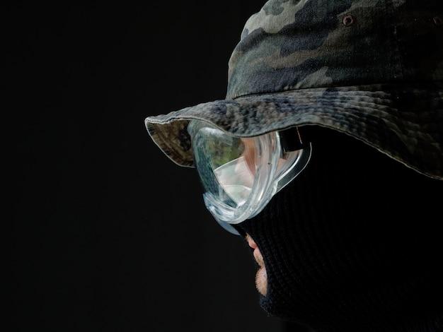 Ein mann in einer schutzmaske, einem tarnhut aus panama und einer schwarzen sturmhaube.