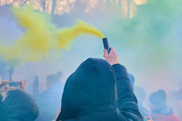 Ein mann in einer schwarzen kapuze hält ein farbiges feuerwerk mit gelber farbe.