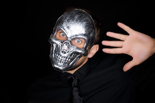 Ein mann in einer skelettmaske zeigt mit seiner hand verschiedene gesten