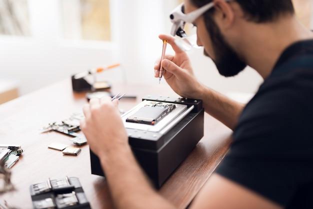 Ein mann in einer speziellen brille hält einen schraubenzieher in der hand.