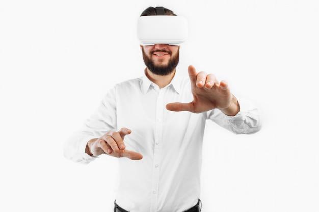 Ein mann in einer virtuellen brille drückt seinen finger auf eine leere stelle an einer weißen wand