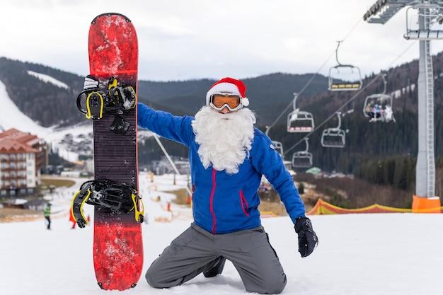Ein mann in einer weihnachtsmütze mit einem snowboard in einem skigebiet.