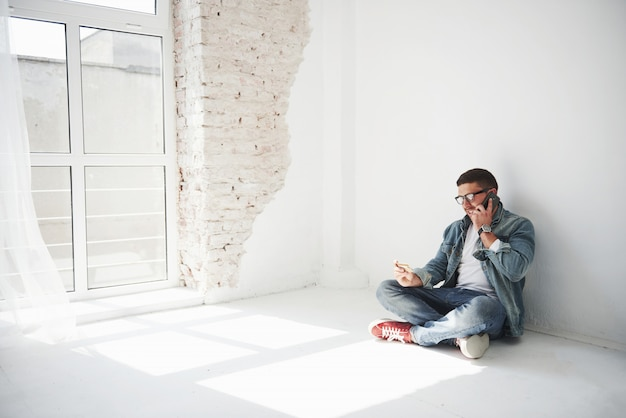 Ein mann in freizeitkleidung sitzt zu hause in einer leeren wohnung und hält eine kreditkarte