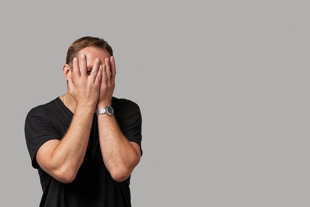 Ein mann in freizeitkleidung versteckt sein gesicht mit den händen