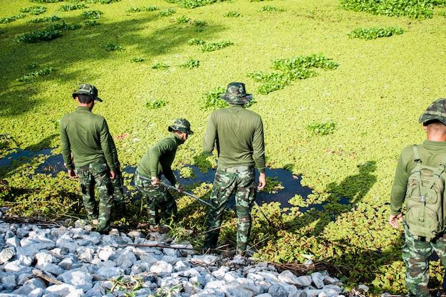 Ein mann in grüner militäruniform reinigen sie die wasserquelle, indem sie unkraut entfernen, das auf dem wasser schwimmt.