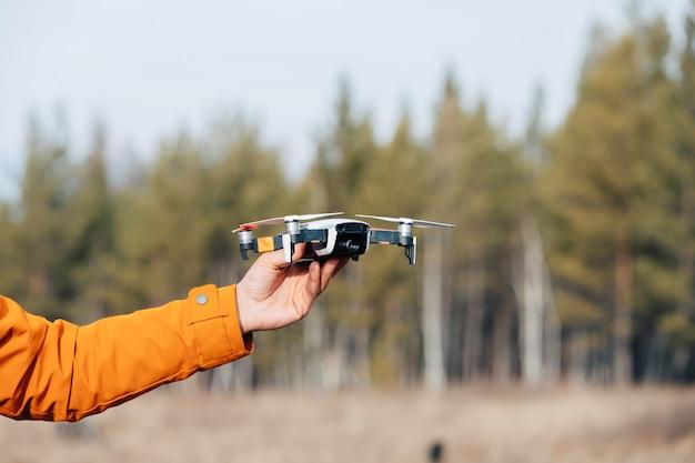 Ein mann in kleidung mit einem orangefarbenen ärmel hält eine fliegende quadcopter-drohne in der hand.