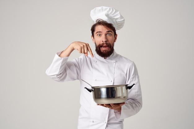 Ein mann in kochkleidung, der einen topf in der hand hält, küchenarbeit, kochen