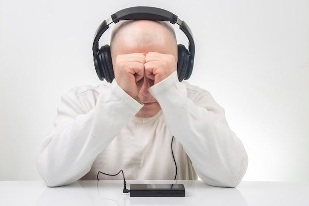 Ein mann in leichter kleidung, der tragbare kopfhörer in voller größe trägt, hört musik mit einem digitalen player.