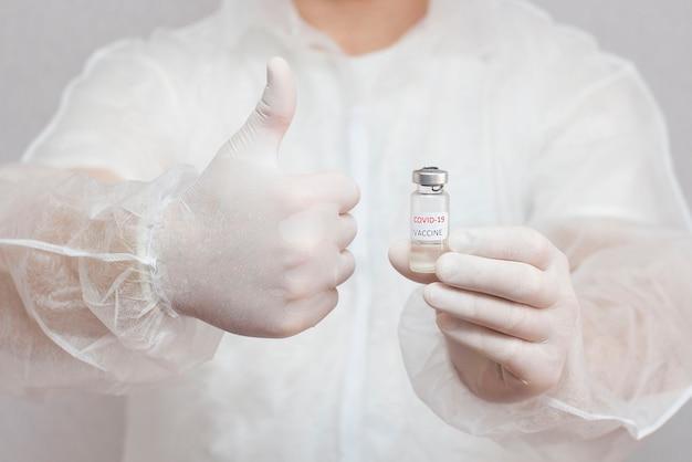 Ein mann in medizinischer uniform hält eine ampulle mit einem coronavirus-impfstoff vor sich und macht mit der hand eine zustimmende geste.