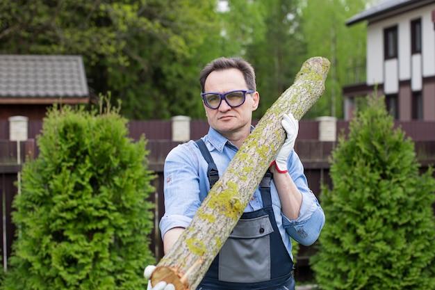 Ein mann in overall und schutzbrille trägt einen baumstamm aus einem wald auf der schulter