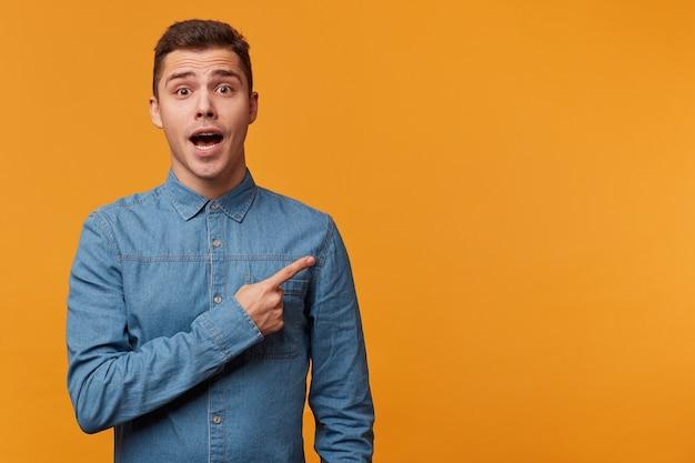 Ein mann in panik, nervös aufgeregt, gekleidet in ein jeanshemd, das mit dem finger nach rechts zeigt, heilt die angst