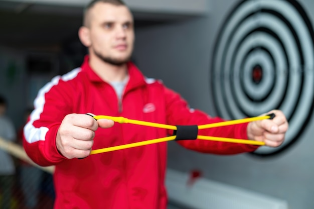 Ein mann in roter jacke übt mit trainingsgeräten für die hände in einem fitnessstudio