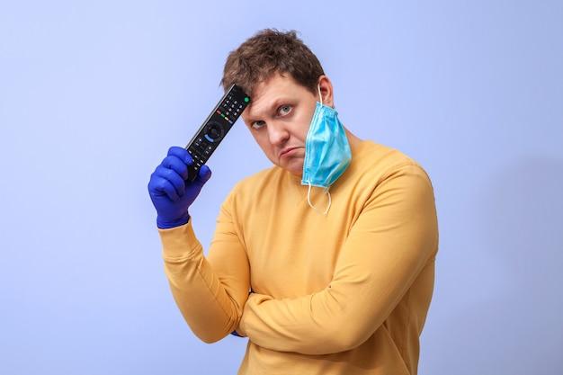 Ein mann in schutzhandschuhen und einer medizinischen maske mit einer tv-fernbedienung in den händen