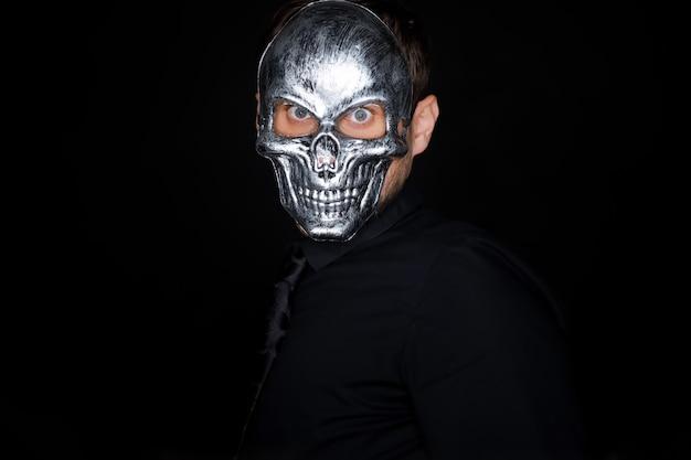 Ein mann in schwarzer kleidung steht auf schwarzem hintergrund und trägt eine skelettmaske