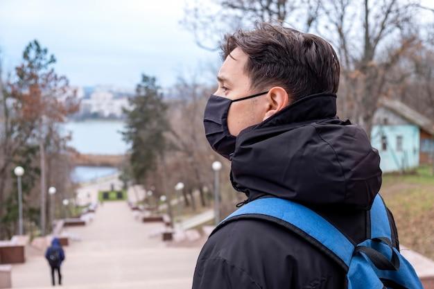 Ein mann in schwarzer medizinischer maske und einer winterjacke mit blauem rucksack, park auf dem hintergrund in chisinau, moldawien