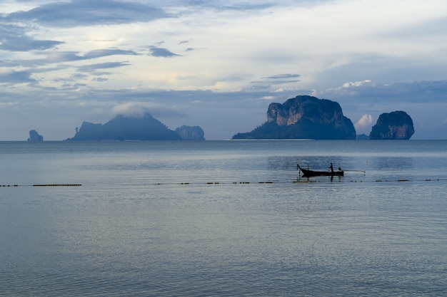 Ein mann in seinem fischerboot, das von seinem morgenfisch während eines schönen morgenlichts am pranang cave beach, railay, krabi, thailand zurückkommt