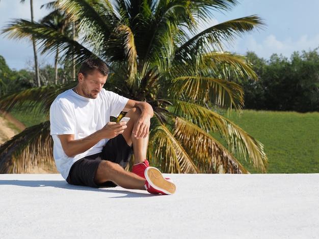 Ein mann in shorts und turnschuhen mit einem handy sitzt auf einem weißen dach. winter auf einer tropischen insel. platz für text.